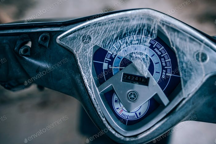 Broken glass of the HUD of the motorbike. Blue color speedometer with fuel gauge and the mile meter.
