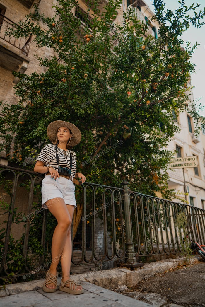 Tourist woman photographer standing under pomegranate tree in old Greek city. Summer vacation