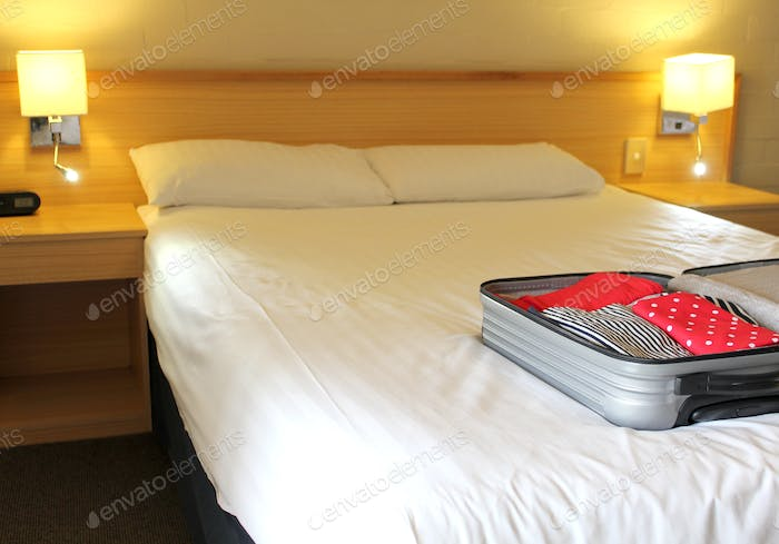 Open suitcase of clothes on a hotel room bed, ready to unpack