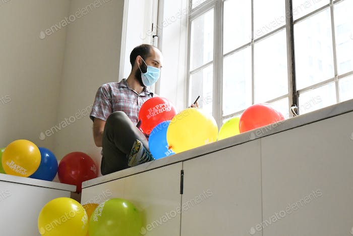 Man sitting by the window with a colorful balloons
