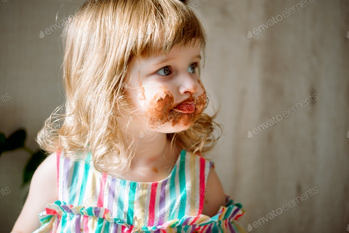 Cute curly redhead baby child shows hands smeared by chocolate