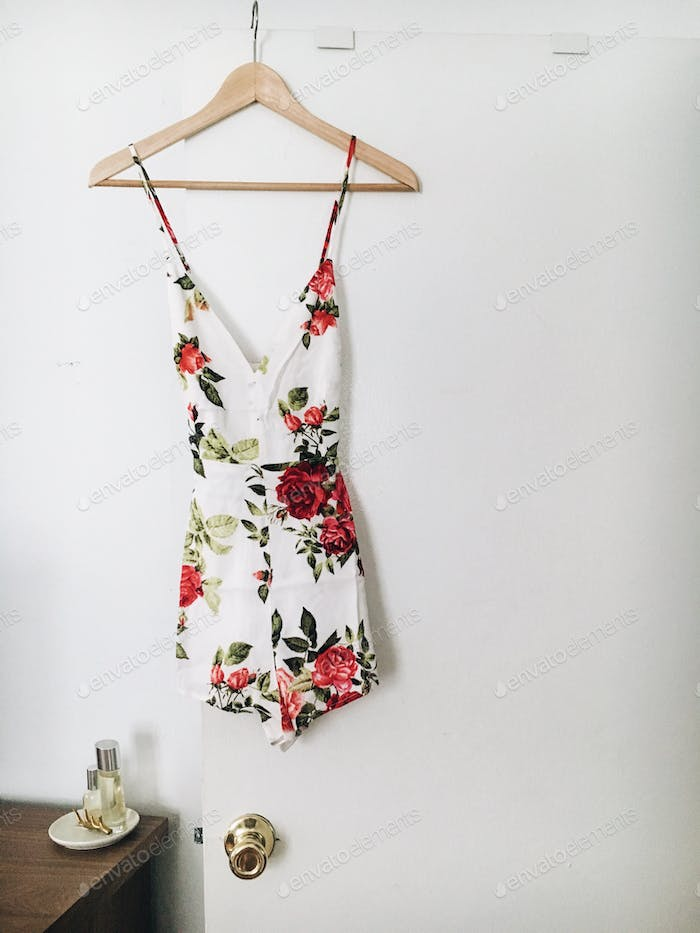 Minimal photo of a floral romper on a wooden hanger in a bright white bedroom