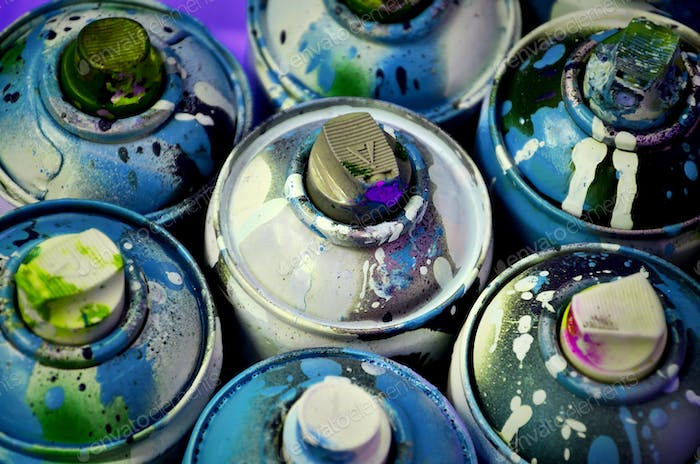 Still life with a large number of used colorful spray cans of aerosol paint lying on the treated