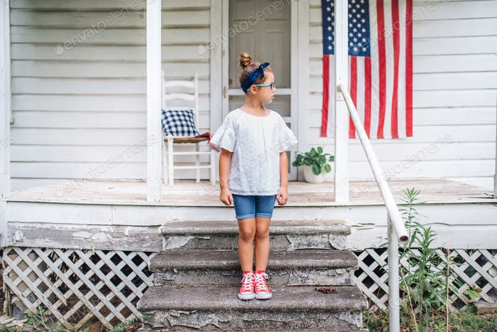 Girl on a front porch. Patriotic.