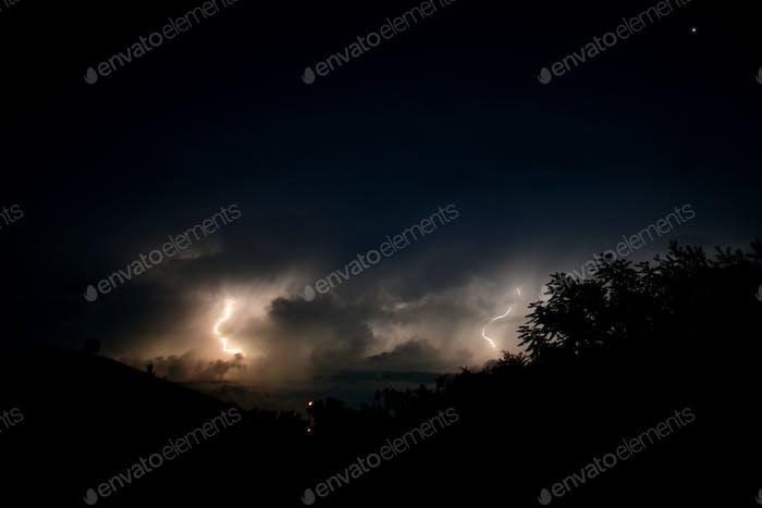 Aufhellung in einem dunklen und wütend aussehenden Nachthimmel mit Sturmwolken.