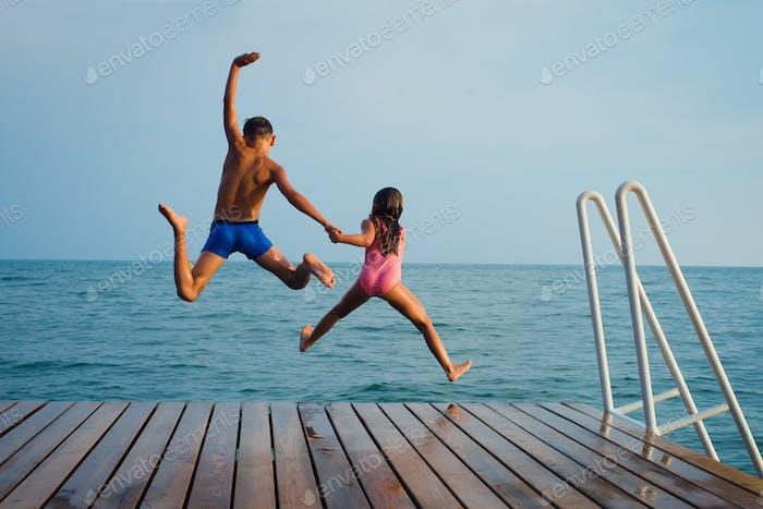 kids jumping in the sea. summer fun.