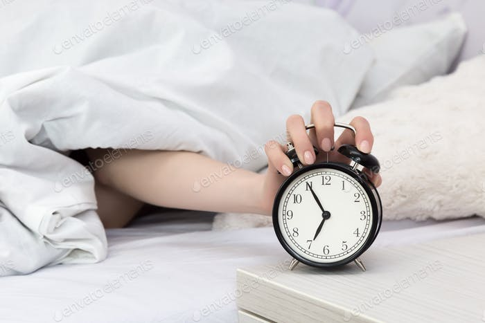 girl in bed in the morning clamps the alarm clock