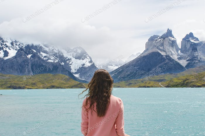 A young woman traveling solo looks across a blue lake in Torres del Paine in Chile