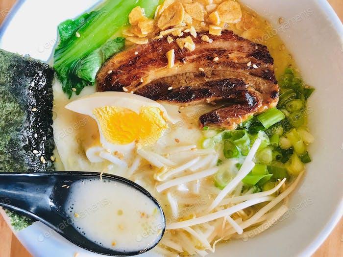 Tonkotsu soup, garlic chips, green onion, ramen egg, pork, baby bok choy, Japanese seaweed, sesame s