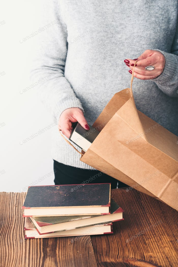 Young woman putting old books to paper bag in antique bookstore