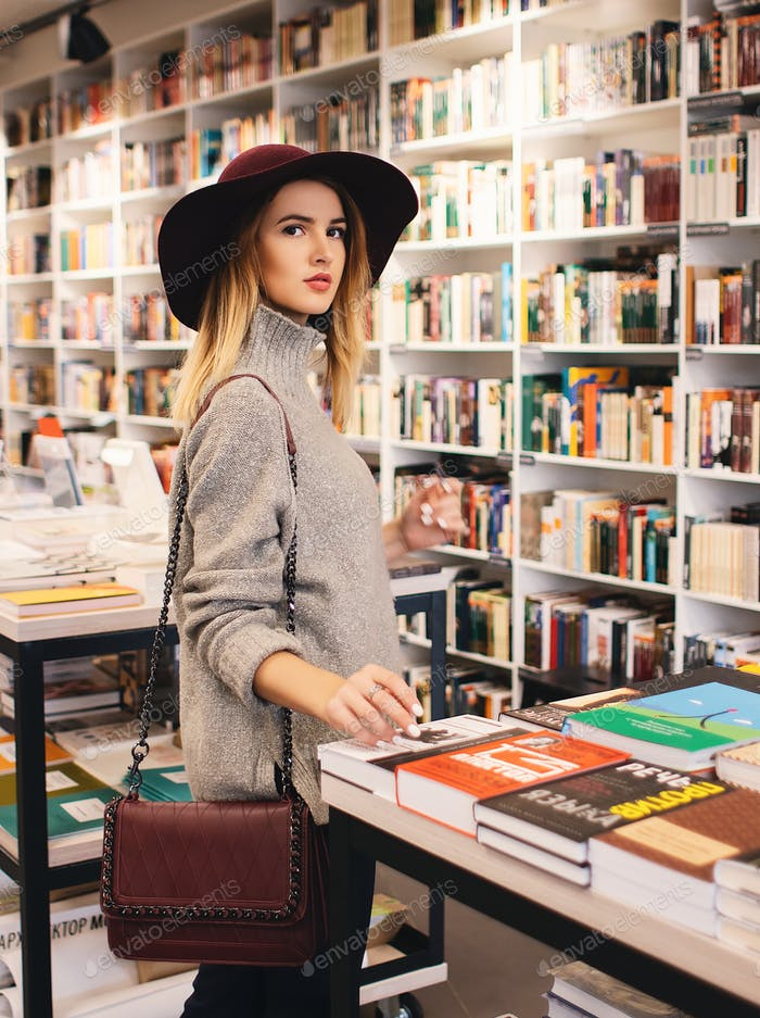 beautiful mysterious blonde girl in hat chooses books in a modern bookstore