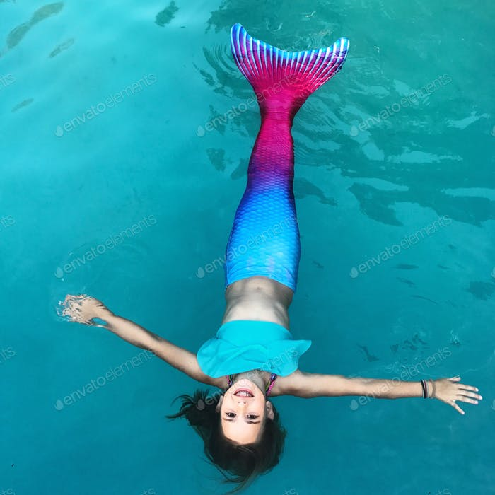young girl wearing a mermaid tail floating in a pool.