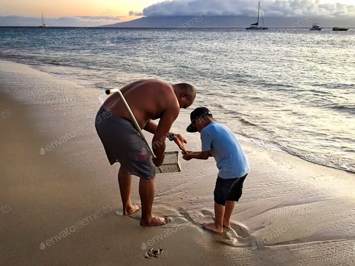 This native Hawaiian dad was teaching his son how to catch sand crabs so that they could use them as