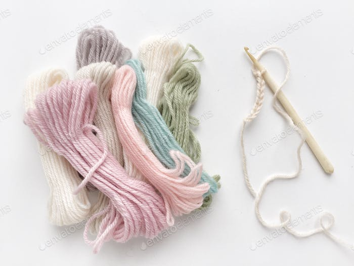 Pastel colored yarn and a crochet hook