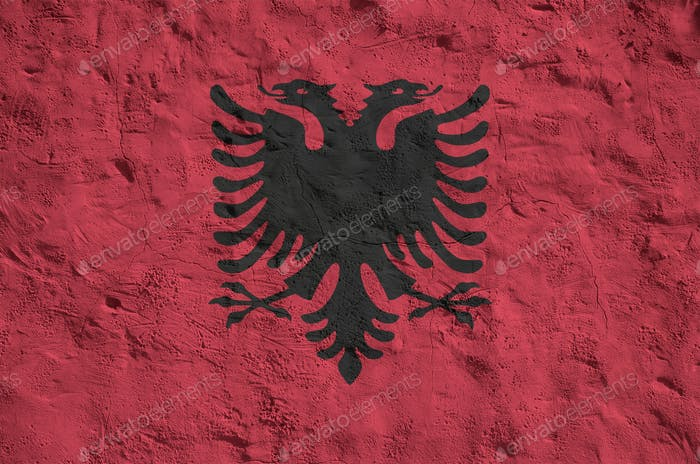 Albania flag depicted in bright paint colors on old relief plastering wall close up