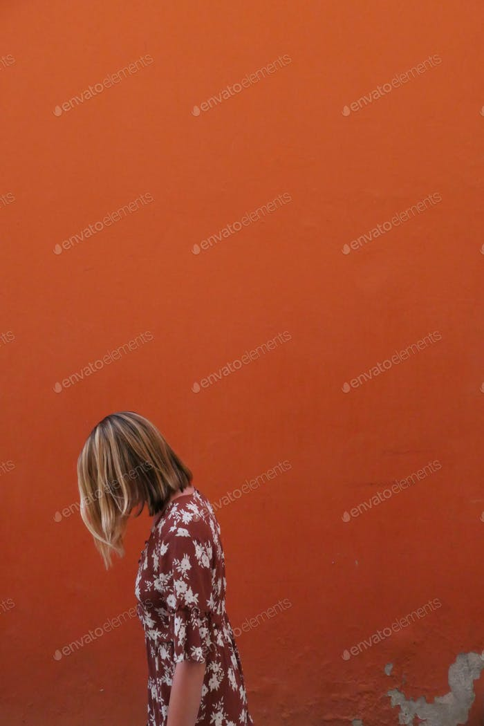A millennial woman in a floral dress. An orange wall in the background