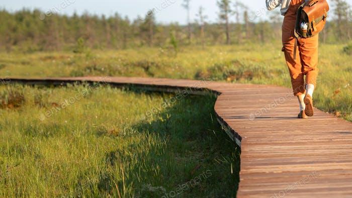 girl naturalist exploring wildlife and ecotourism adventure walking on path through peat bog swamp