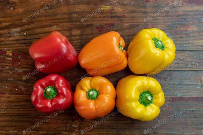 Fresh colorful bell peppers on distressed wooden table