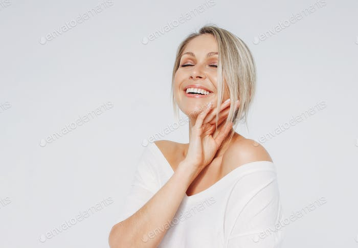 Beauty portrait of blonde smiling laughing woman 35 year plus clean fresh face with close eyes