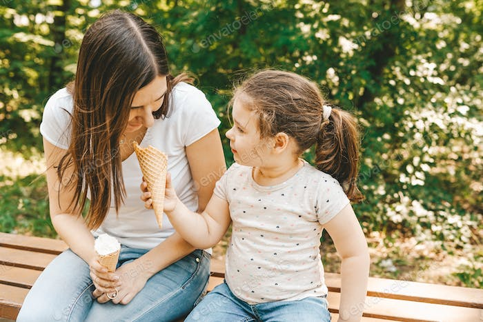 Cute toddler girl with her mother eating ice cream outdoor in the sunny summer day