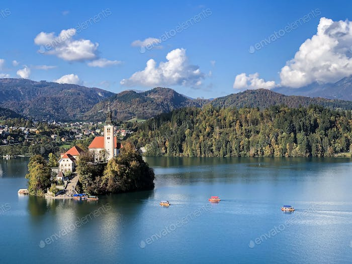 Beautiful view of Bled island at lake Bled with hills and villages on background