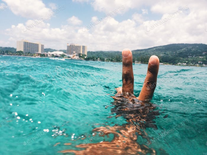 open water — man holding up a peace sign in the middle of the ocean