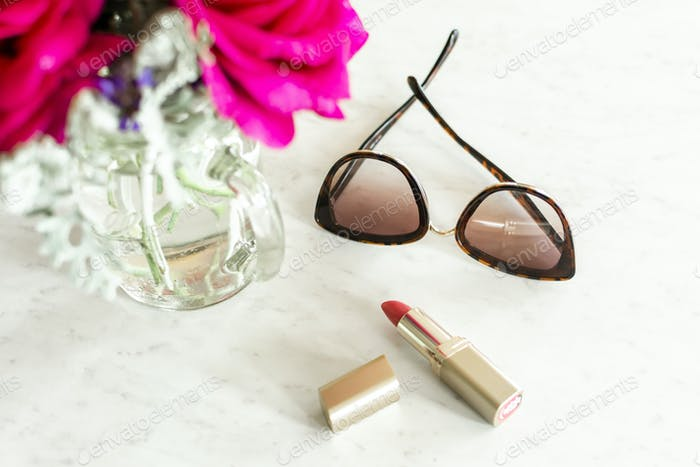 Sunglasses and lipstick on the counter with fresh flowers