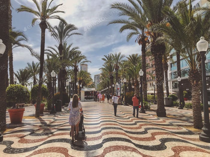 Woman walking with buggy on designed mosaic wavey patterned tiles with palm trees.