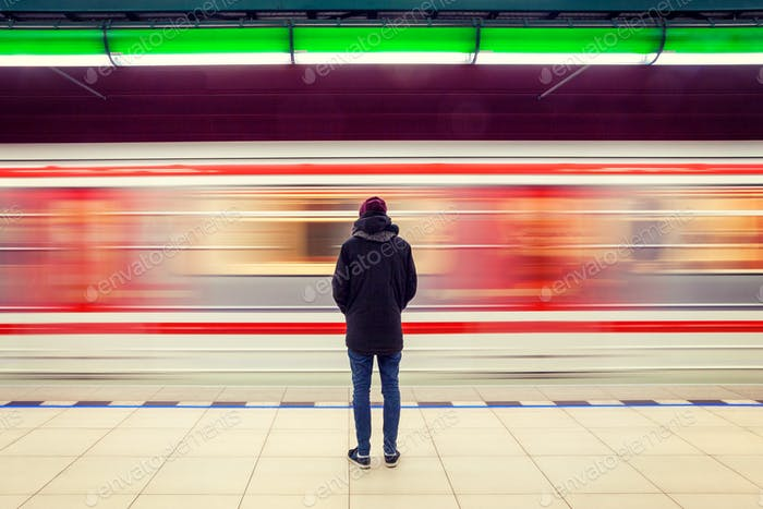 Lonely man from behind at subway station with moving train in background, motion blur