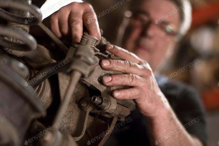 ↟ Professional car mechanic working in an automobile workshop near a car