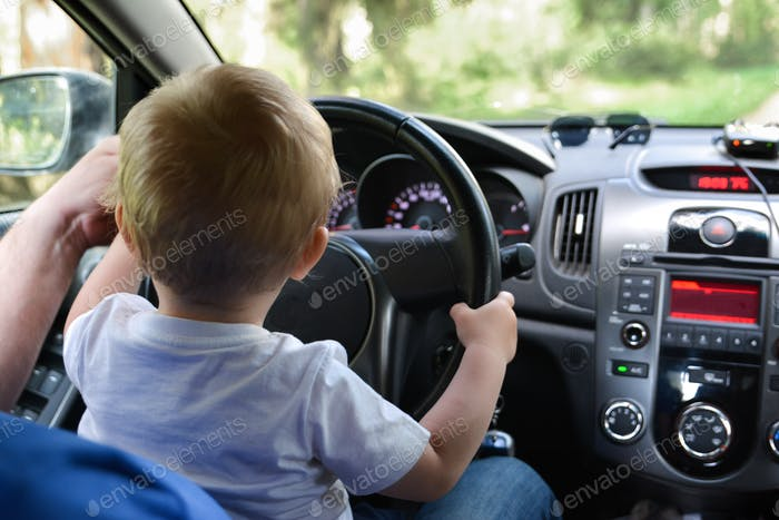 A little baby is sitting on the lap of father and holds the steering wheel of the car