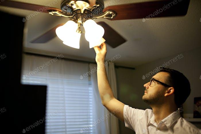 Mann ändern eine Glühbirne in einem Ventilator zu Hause