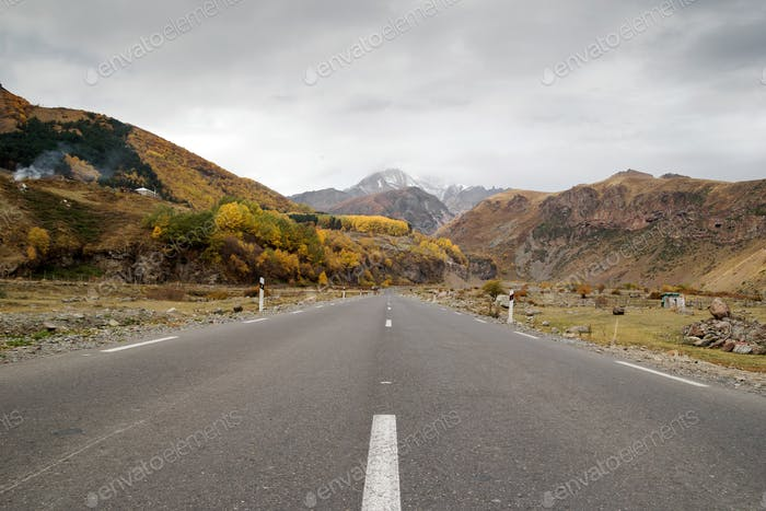Empty road between Caucasus Mountains in autumn time.
