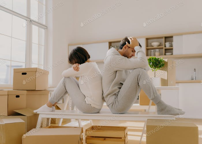 Stressful couple get divorce, leave house, start living separately, sit backs to each other,