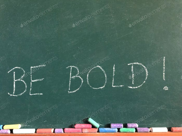 The words Be Bold! written on a chalkboard with coloured chalk sticks and copy space