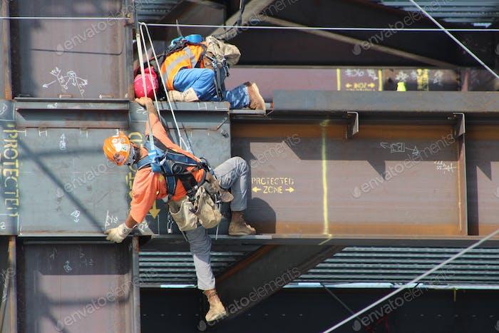 Trabajadores de la construcción fuertemente equipados en una obra de construcción.