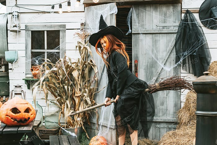 girl in a witch costume with a broom at a Halloween party