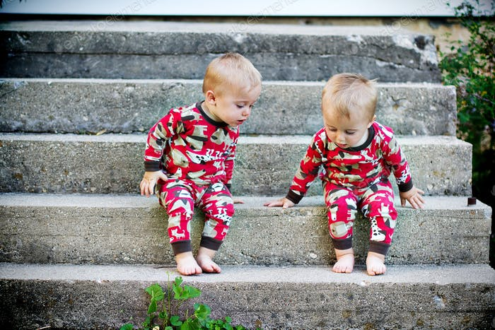 Twin brothers being curious outside at home