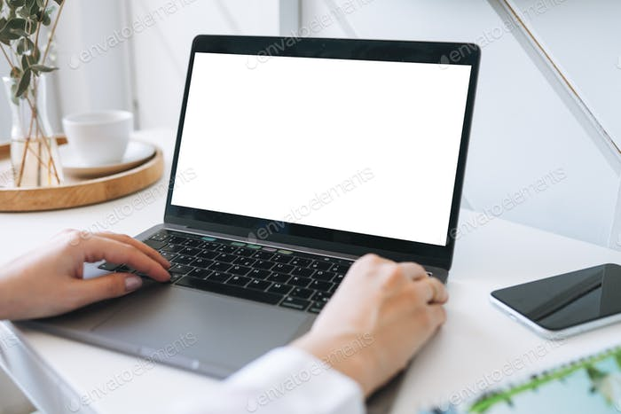 Young woman in white shirt using laptop with white screen on table at home, mockup