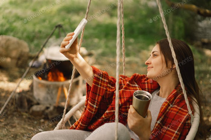 Beautiful Girl wrapped in red plaid drinking tea and use phone in a cozy hanging chair outdoors.