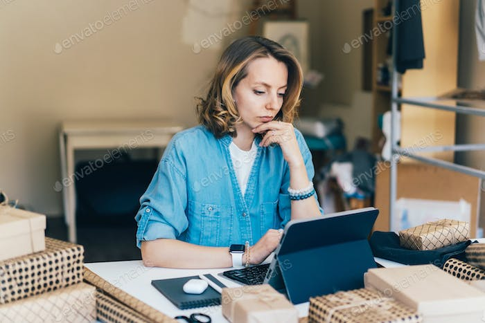 businesswoman thinking with concentration working at home on laptop