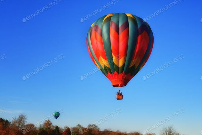 Colorful hot air balloons floating flying soaring through a beautiful blue sky.