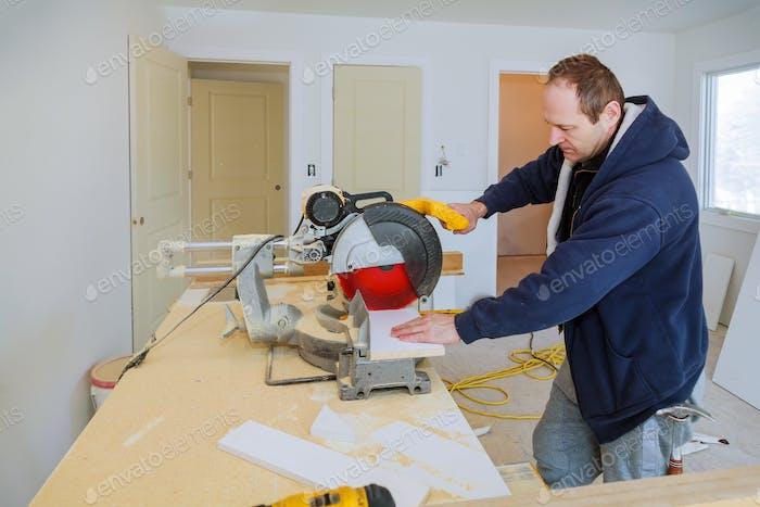 Baumeister verwendet Kreissägewerkzeug, um Holzsockelleimen zu schneiden