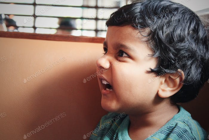 Annoyed kid in bad mood and misbehaving