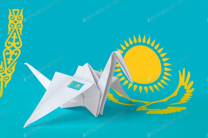 Kazakhstan flag depicted on paper origami crane wing. Oriental handmade arts concept