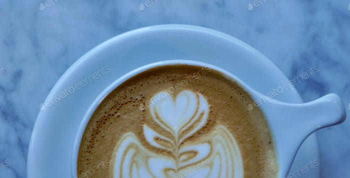 Overhead partial view of a perfect Rosetta latte art in a white coffee cup