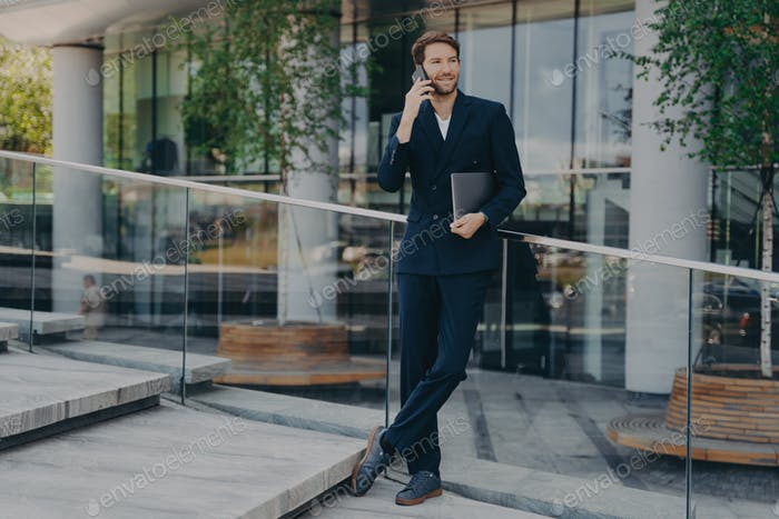 Elegant businessman in formal clothes has telephone conversation holds digital gadget under arm