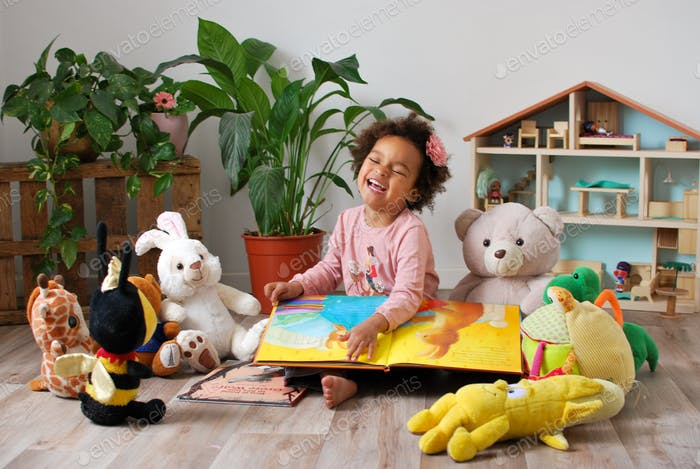 Little diverse girl (mixed origine) reading a book for her teddy bears / cuddly toys in her bedroom