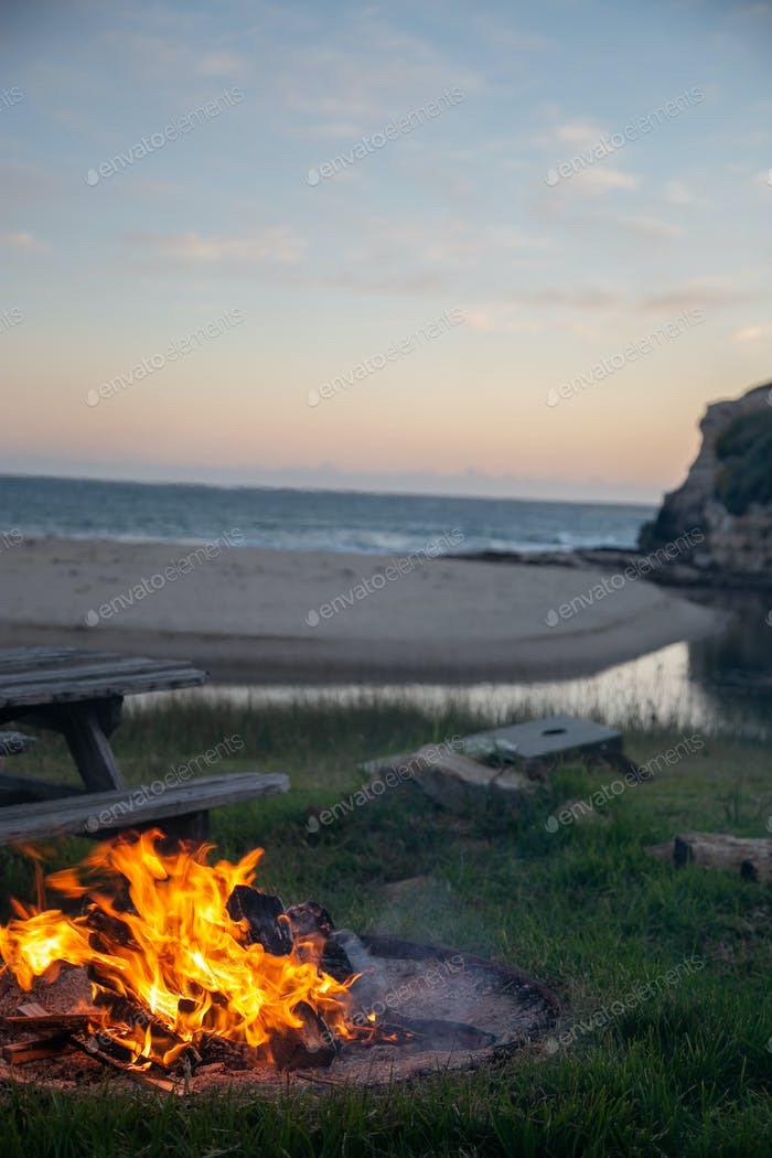 Campfire flame during sunset at the beach while camping in the summer