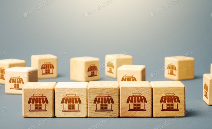 Blocks symbolizing shopping stores. Building a successful business empire. Franchise concept. Mergin